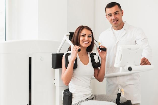 Médico y paciente femenino posando junto a la máquina médica