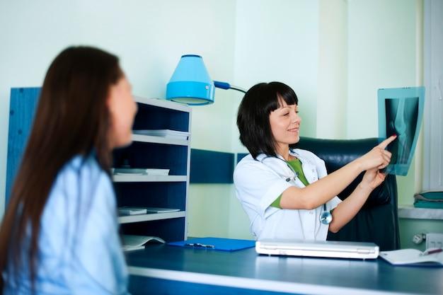 Médico y paciente mirando rayos x