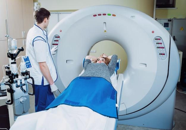 . médico y paciente en la sala de tomografía computarizada.