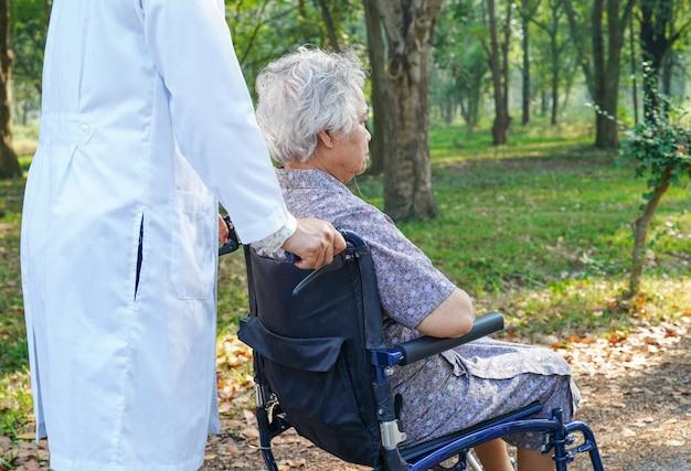 Médico y paciente senior asiático con cuidado en silla de ruedas en el parque.
