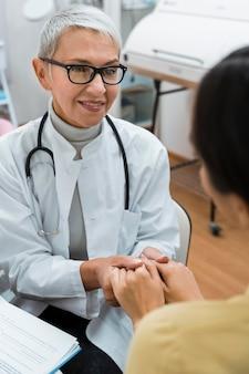 Médico y paciente tomados de la mano después de buenas noticias