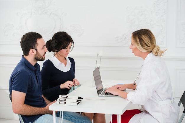 Médico y pacientes de la joven pareja en la oficina