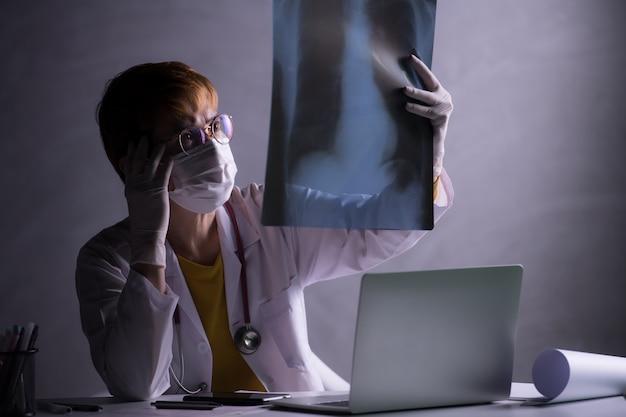 El médico parece preocupado al inspeccionar la película de rayos x de los pulmones durante la crisis del brote pandémico covid-19