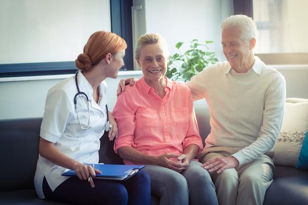 Médico y pareja senior interactuando entre sí