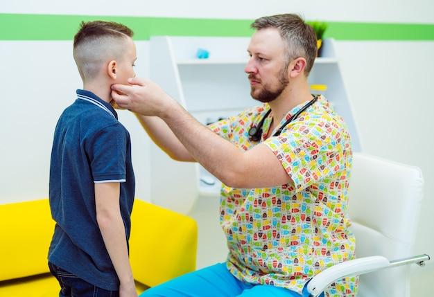 El médico pediatra comprueba los ganglios linfáticos del niño.