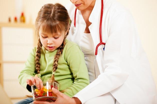 Médico pediatra dando dulces al pequeño paciente