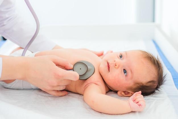 Médico pediatra examina a niña con estetoscopio
