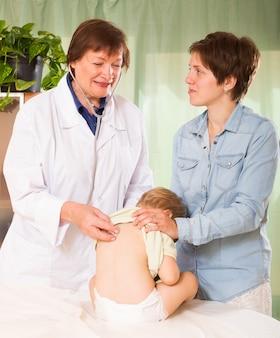 Médico pediatra examinando bebé niña