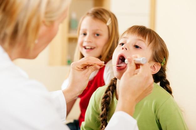 Médico pediatra examinando la garganta de la niña