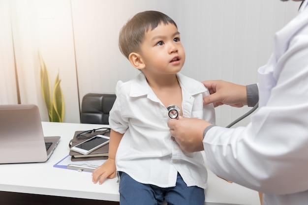 Médico pediatra examinando a un niño asiático por el estetoscopio