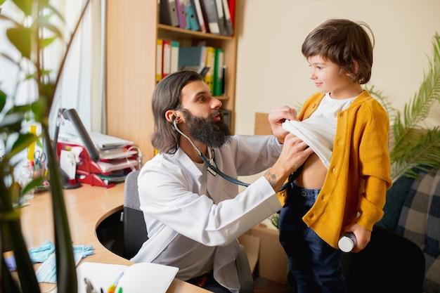Médico pediatra examinando a un niño en el consultorio médico comfortabe