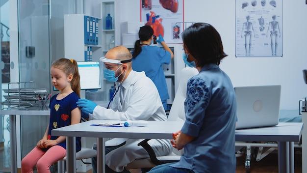Médico pediatra con máscara de protección y estetoscopio escuchando aliento de niña. médico especialista en medicina que brinda servicios de atención médica, consulta, tratamiento durante el covid-19 en el hospital
