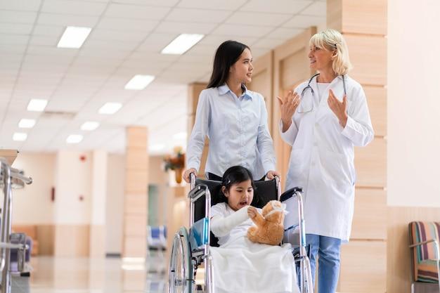Médico pediatra y paciente infantil en silla de ruedas con su madre en el centro médico de salud