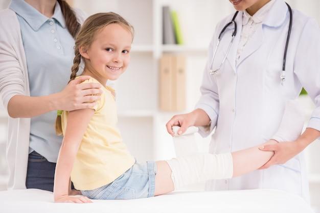 Médico pediatra vendar la pierna del niño.