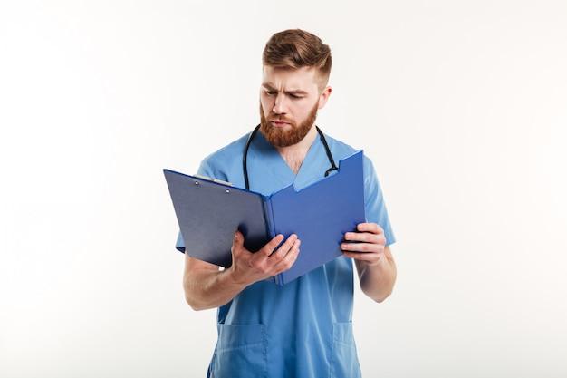 Médico pensativo o enfermera con estetoscopio mirando portapapeles