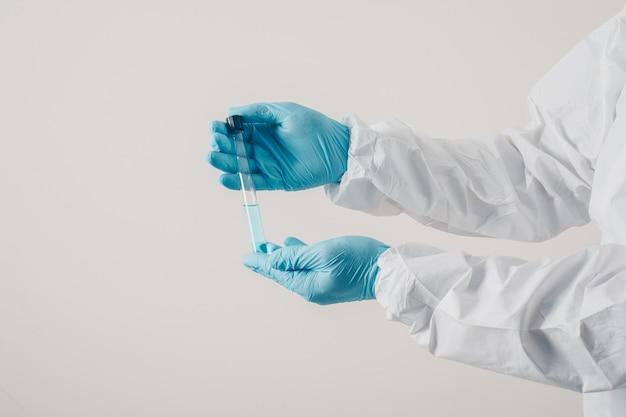 Un médico de pie y sosteniendo la medicina en guantes médicos y traje protector en fondo claro.