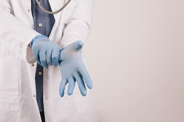 Médico poniéndose los guantes