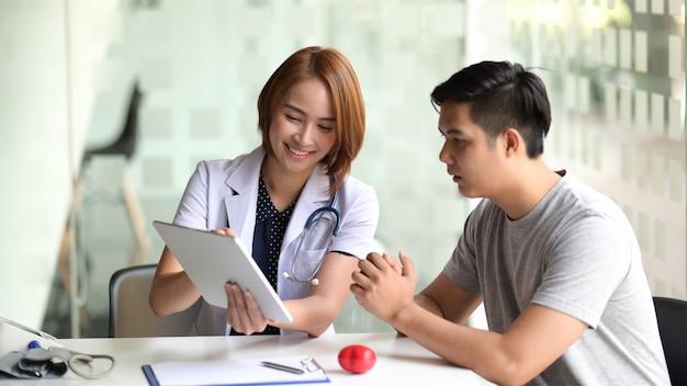 Médico presentando a un paciente información sobre una tableta digital.