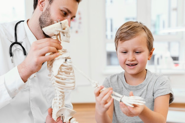 Médico de primer plano y niño con esqueleto