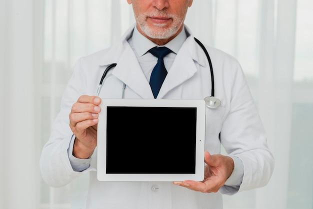Médico de primer plano que muestra la maqueta de la pantalla de la tableta