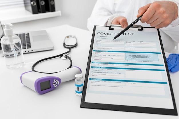 Médico de primer plano que presenta formulario médico covid