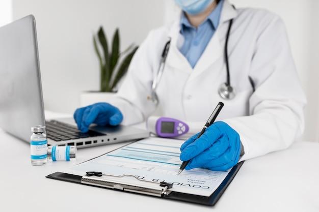 Médico de primer plano trabajando en equipo portátil