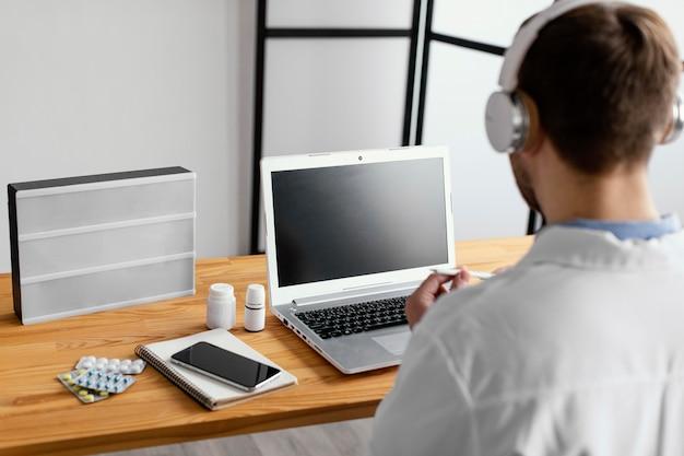 Médico de primer plano usando audífonos