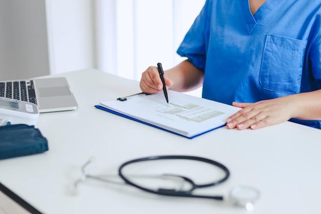 Médico profesional en bata de uniforme blanco entrevista al paciente consultor.