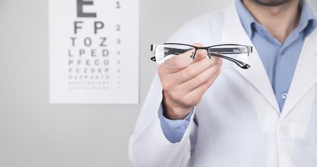 Médico profesional caucásico mostrando anteojos.