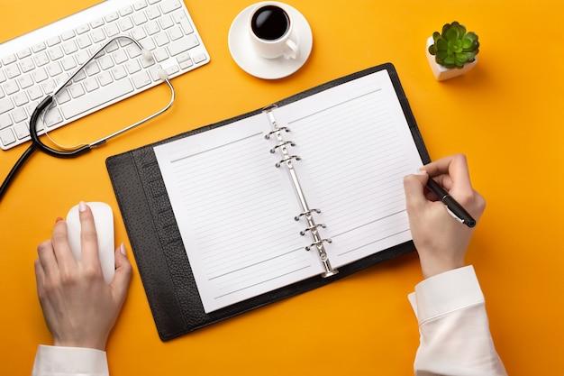 Médico profesional escribiendo registros médicos en un cuaderno con estetoscopio, teclado, taza de café y mouse