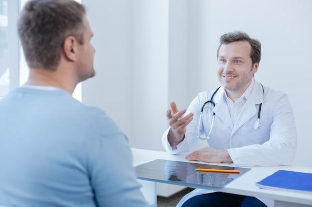 Médico profesional guapo alegre que trabaja y disfruta de la conversación con el paciente en la clínica mientras comparte alegría