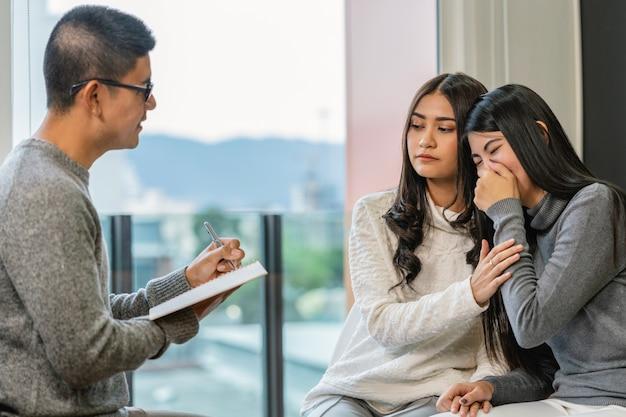 Médico profesional masculino asiático del psicólogo que da la consulta a los amantes lesbianos pacientes