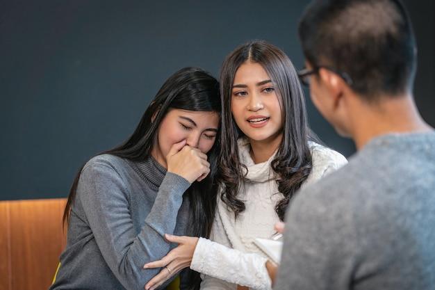 Médico profesional masculino asiático del psicólogo que da la consulta a los pacientes de los amantes