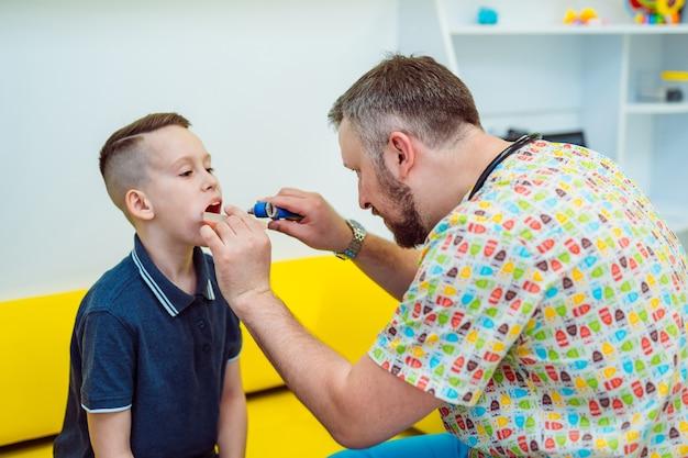 Médico profesional masculino comprueba los ganglios linfáticos de un niño en el centro médico.