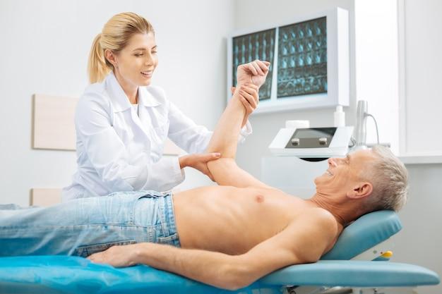 Médico profesional. mujer encantadora alegre positiva sosteniendo el brazo de su paciente y sonriendo haciendo chequeo médico