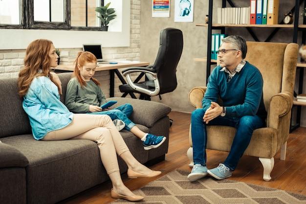 Médico profesional. psicólogo profesional serio hablando con sus pacientes mientras tiene una sesión con ellos.