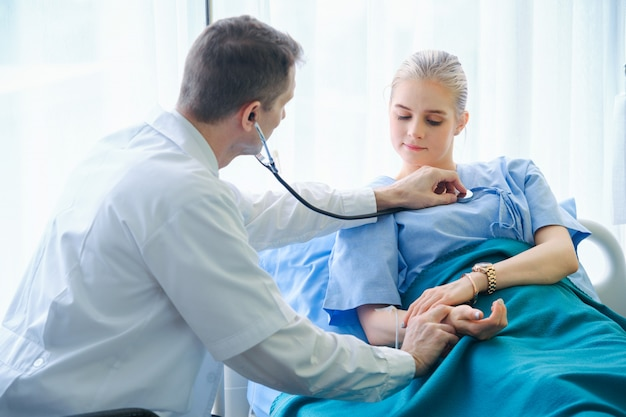 El médico profesional está utilizando un estetoscopio para examinar los latidos del corazón del paciente. el médico analiza el latido del corazón del paciente para un diagnóstico preliminar y observación.