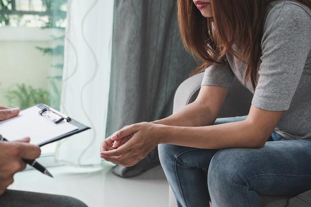 Médico psicólogo profesional sosteniendo el portapapeles y llenando información médica del paciente consultando a su paciente deprimido