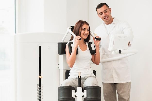 Médico que muestra cómo usar un dispositivo médico para una paciente