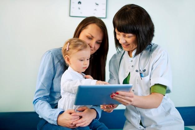 Médico que muestra los resultados médicos de la madre en la tableta