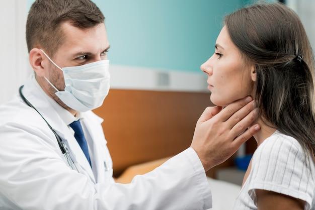 Médico que proporciona examen de garganta