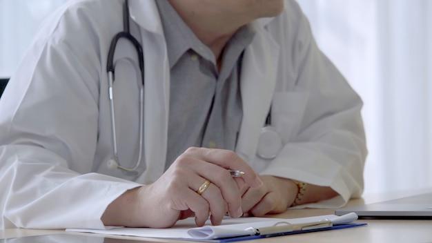 Médico que trabaja con datos de salud del paciente en la oficina del hospital