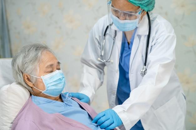 Médico que usa estetoscopio para controlar a una paciente asiática mayor que usa una mascarilla para proteger el coronavirus covid19