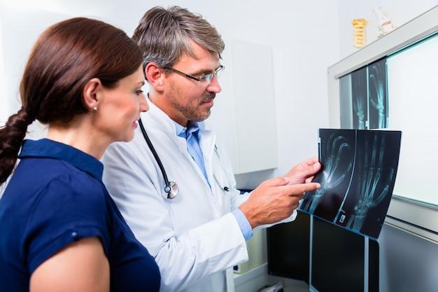 Médico con radiografía de la mano del paciente.