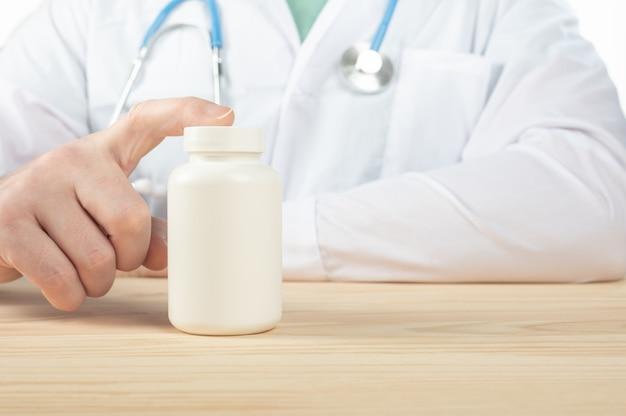 El médico recomienda tomar medicamentos, suplementos, vitaminas, suplementos alimenticios. practicante con botella de pastillas