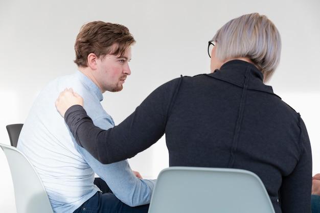 Médico de rehabilitación femenina consolando paciente masculino