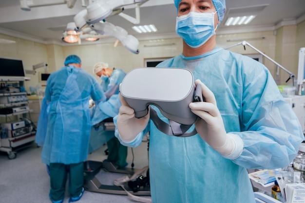 Médico en una sala quirúrgica con gafas de realidad virtual en el fondo de la operación real.
