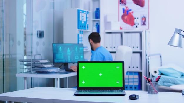 Médico de salud dejando el gabinete de la clínica y la computadora portátil con espacio de copia disponible mientras la enfermera escribe notas en la computadora. cuaderno con pantalla reemplazable en clínica médica.
