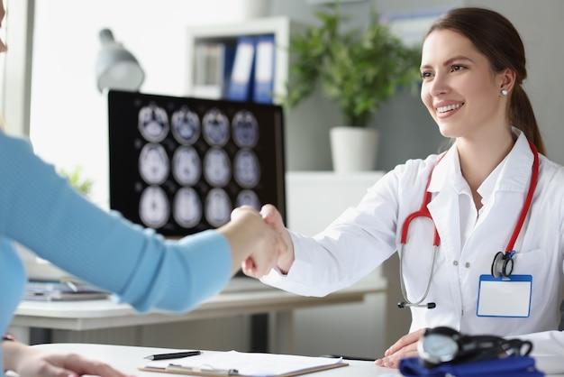 Médico saludando al paciente en el hospital con apretón de manos