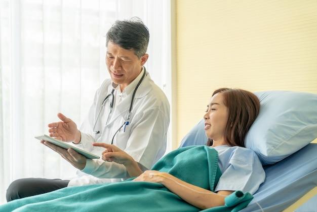 Médico senior asiático sentado en la cama de un hospital y discutiendo con paciente femenino